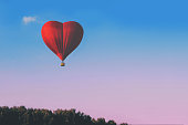 istock Red hot air balloon in the shape of a heart against the blue sky. Banner. 1200380563