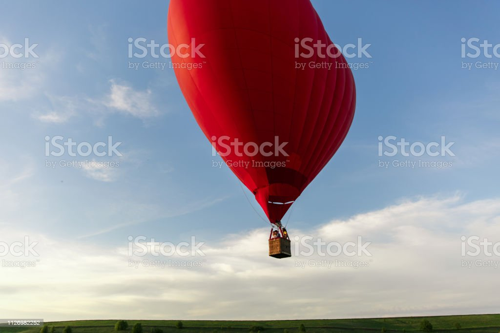 Red hot air balloon in the shape of a heart fly in sky. Love,...