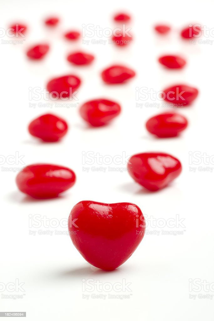 Red hot Candy Cinnamon hearts on white vertical royalty-free stock photo
