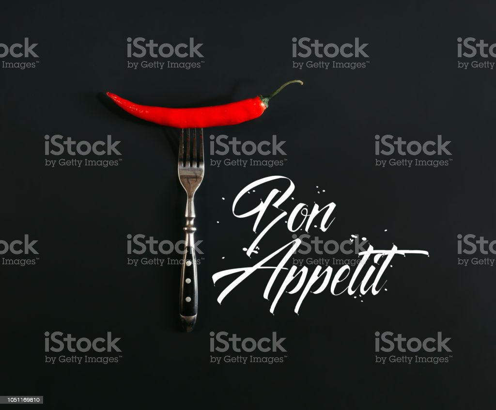 red hot chili pepper on fork on black with 'bon appetit' lettering stock photo