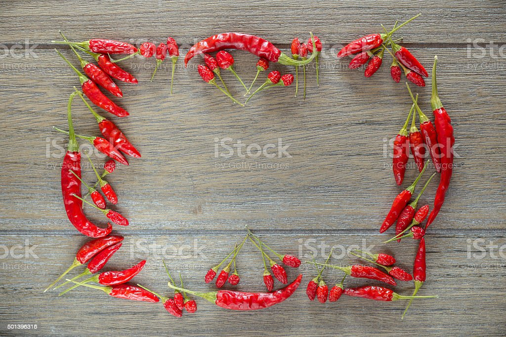 Red hot chili peppers framed on old wooden table stock photo