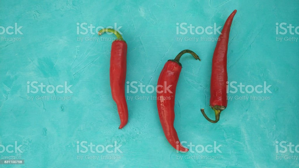 Red hot chili peppers on teal background stock photo