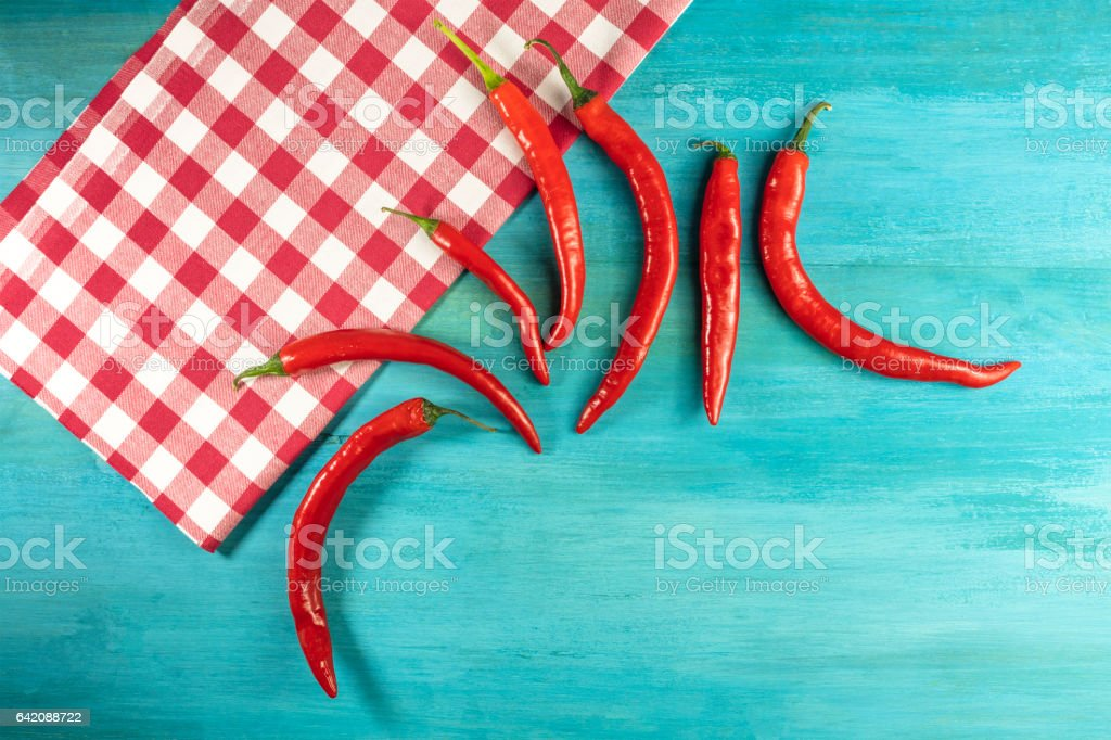 Red hot chili peppers on turquoise with copyspace stock photo