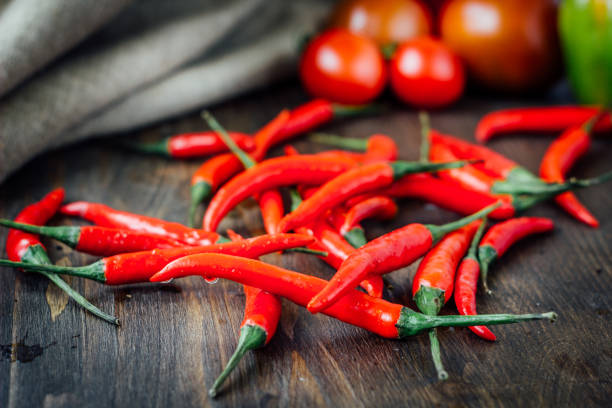 Red hot chili peppers over rustic wooden table. stock photo