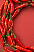 istock red hot chili peppers, popular spices concept - colorful semicircle composition by hot chili pepper pods on red background, top view, flat lay, free space for text, vertical 860840986