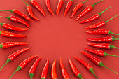 istock red hot chili peppers, popular spices concept - decorative circle made from beautiful red hot chili pepper pods on red background, in the middle is free space for text, top view, flat lay 860845138