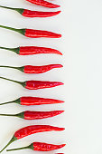 istock red hot chili peppers, popular spices concept - decorative pattern in the form of a horizontal pods of red hot pepper on a white background, top view, flat lay, vertical 676657596