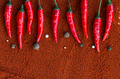 istock red hot chili peppers, popular spices concept - decorative pattern of chili pods on a brown background from a powder of red indian curry, flat lay, free space for text 680250996
