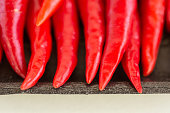 istock red hot chili peppers, popular spices concept - macro sharp tips of the red chili peppers, fresh clean juicy pods on the dark packaging at store, top view, flat lay 680249250