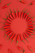 istock red hot chili peppers, popular spices concept - ring of red pepper pods, beautiful circle composition on red background of fresh chili, top view, flat lay, vertical 676668380