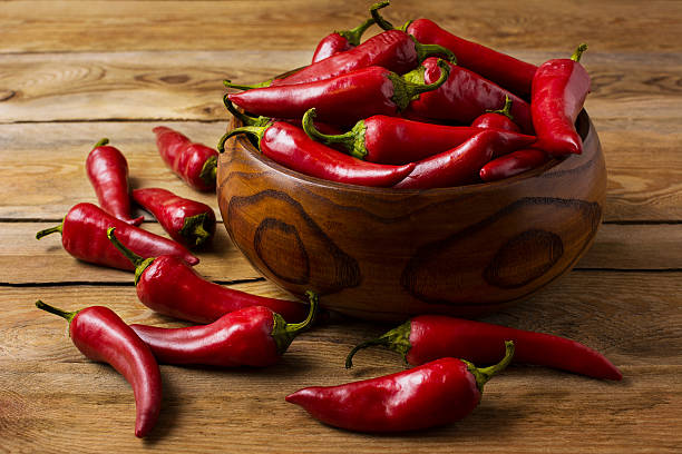 red hot chilli pepper in wooden bowl - pfeffer stock-fotos und bilder