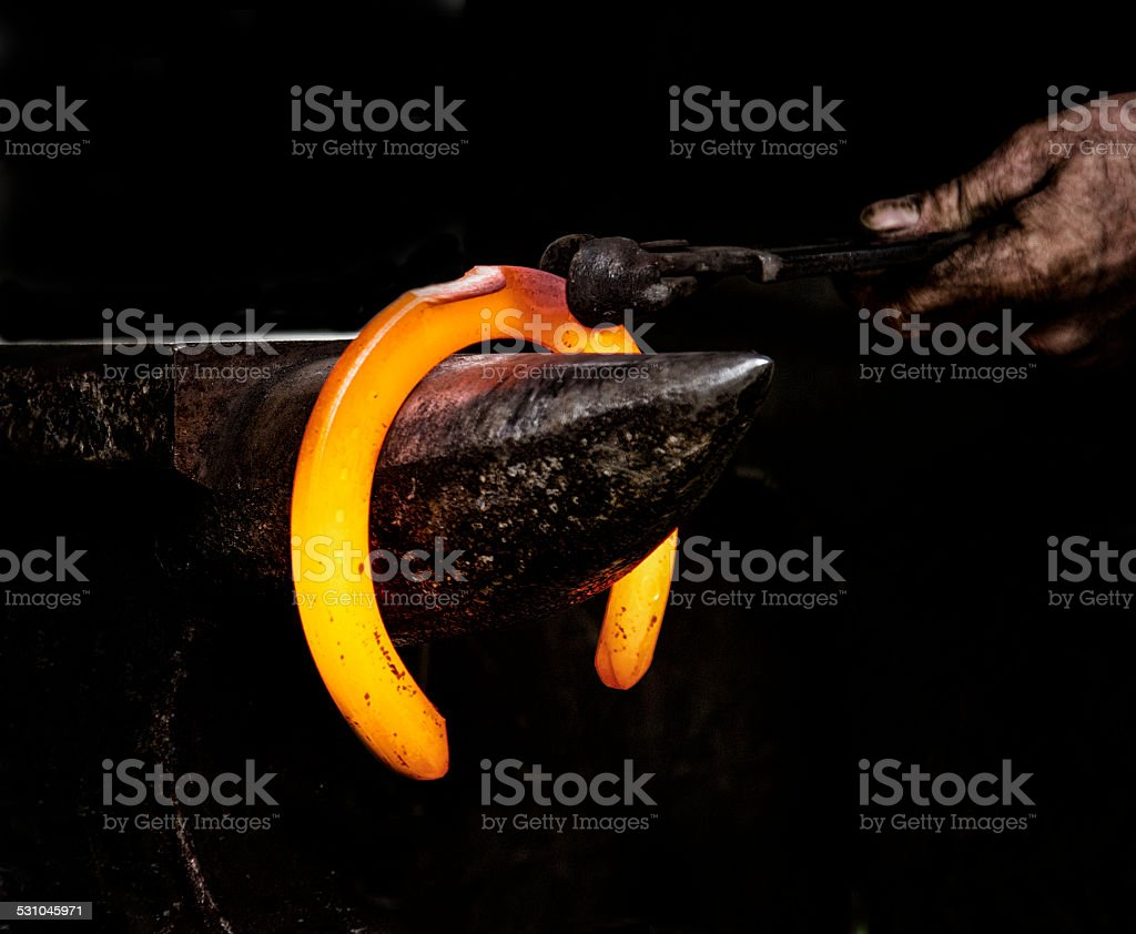 red hot horse shoe on anvil stock photo