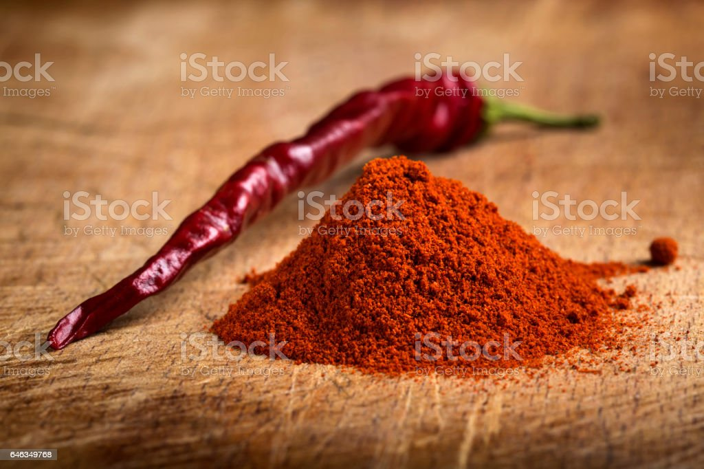 Red hot paprika powder heap and one dried chilli stock photo