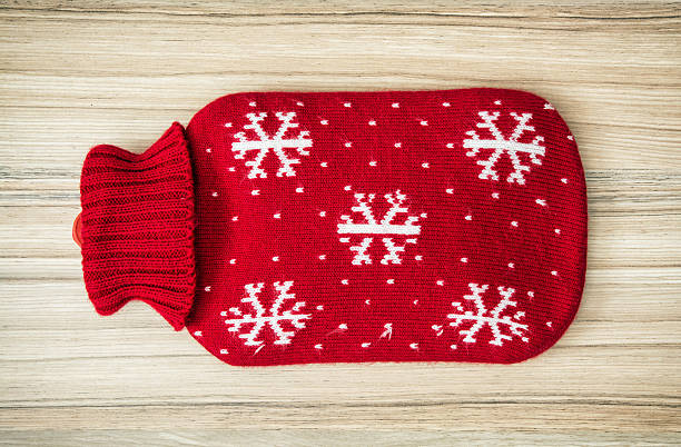 Red hot water bottle Red hot water bottle on the wooden background. hot water bottle stock pictures, royalty-free photos & images