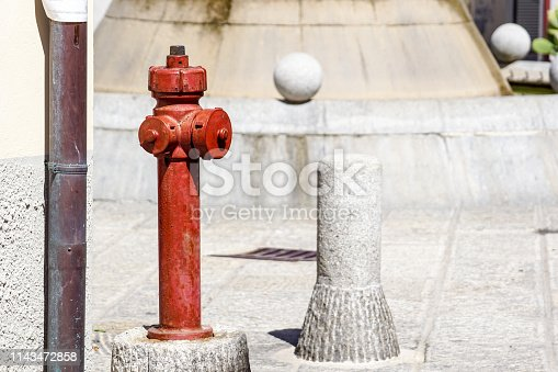 Red hydrant on the city street . Detail .