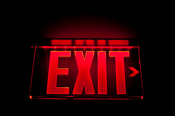 a red illuminated exit sign on black - exit sign stock photos and pictures