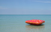 Red Inflatable ring or float in the blue sea with beautiful blue sky. Summer or holiday concept.