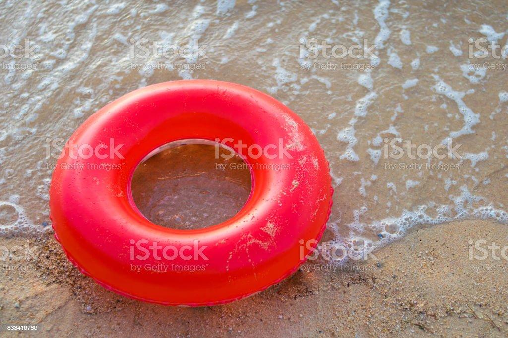 red inner tube on the beach stock photo