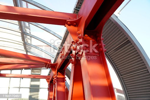 Red iron beams bolted on. Connection of several iron beams in one place. Indoor overhead pedestrian crossing with iron construction and glass ceiling.