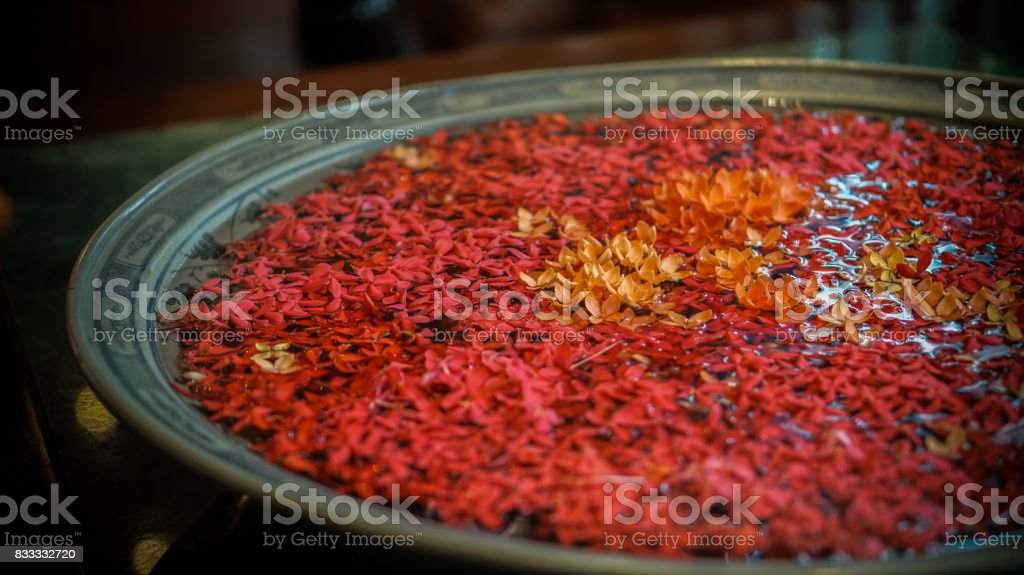 red ixora flower floating in clay pot at thai message spa stock photo