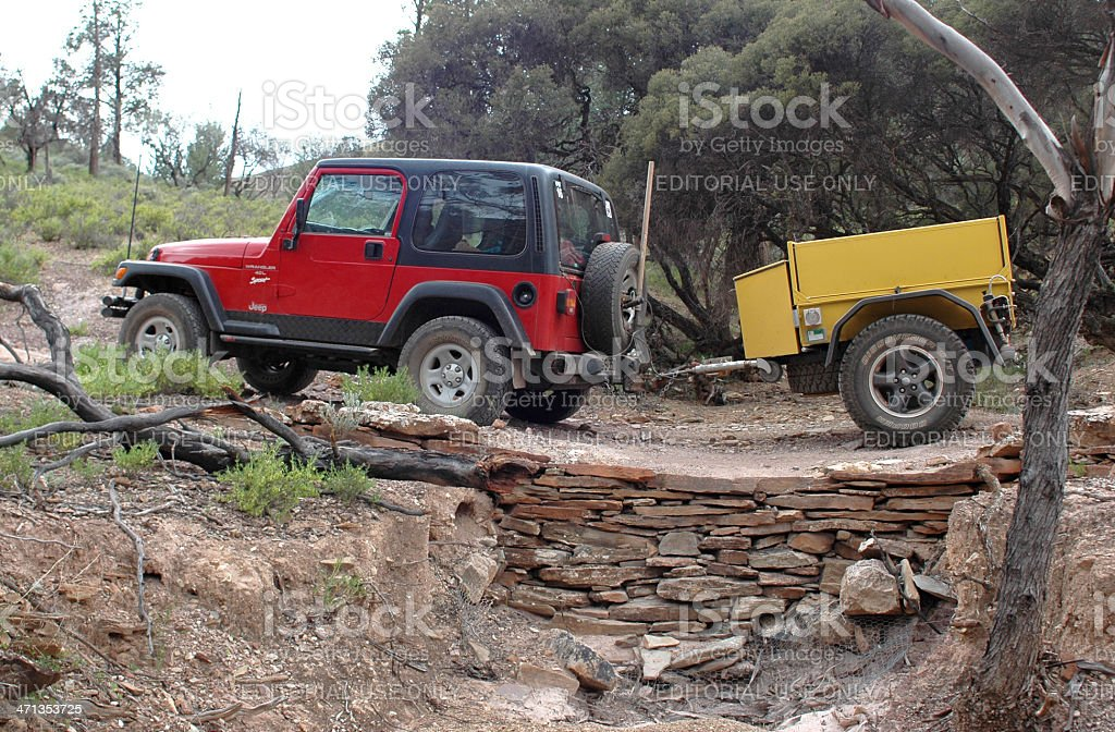 Red Jeep pulling yellow offroad trailer through Flinders Ranges stock photo