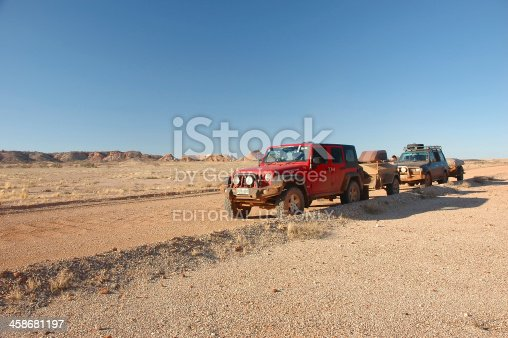 Coober Pedy, South Australia - July 16, 2010: Red Jeep Wrangler + Toyota Landcruiser driving through the outback towing camper trailers. Big 4x4 vehicles are needed to see remote parts of Australia