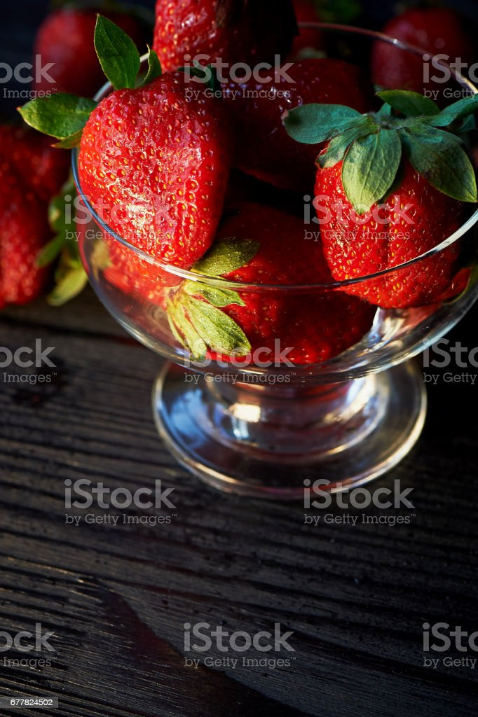 Red juicy strawberry on a dark black wooden background. The droplets of water. Juiciness, vitamins and healthy food. Glass vase royalty-free stock photo