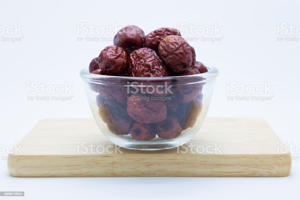 Red jujube on glass cup over wooden board stock photo