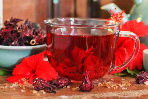 roten karkadeh rote sauerampfer hibiskustee im glaskrug mit trockenen tee cu - rosen tee stock-fotos und bilder