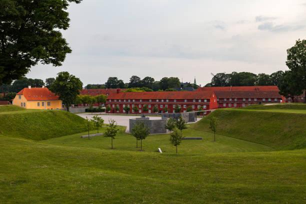 Red Kastellet (Citadel) barracks and green meadows around. Copenhagen, Denmark stock photo