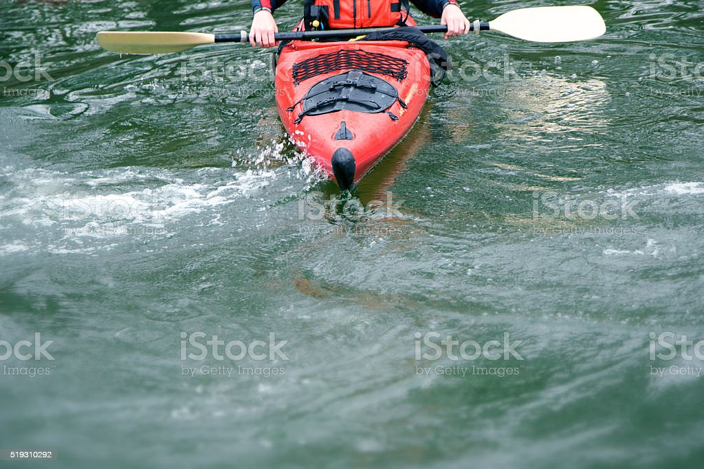 red kayak in rough water, front view, boat detail of prow and paddle,...