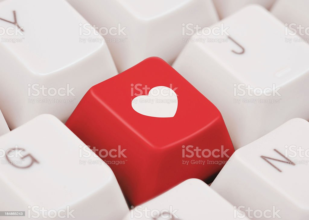 Red key with heart symbol on computer keyboard stock photo