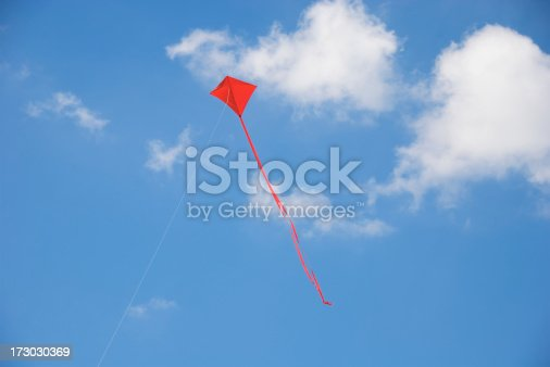 Single red kite flies with a streaming tail against blue sky and white clouds