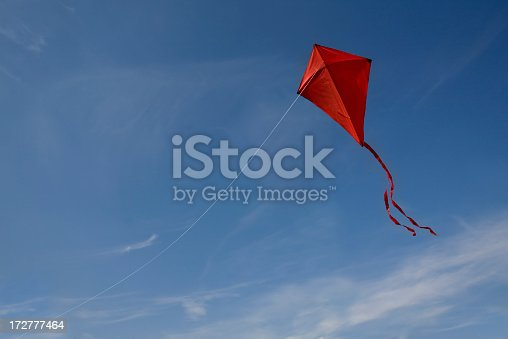 A red kite with a string flying against a blue sky.