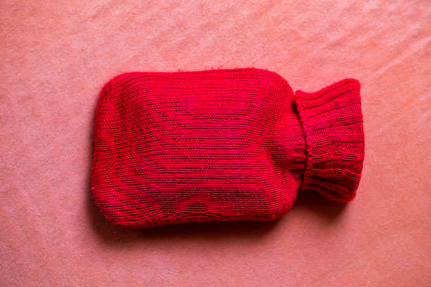 red knit hot water bottle  on pink background. stock photo