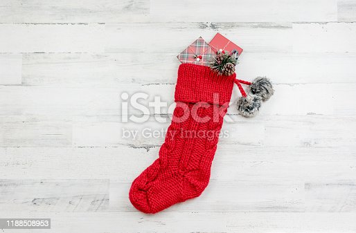 Chunky  knit red Christmas stocking with pom pons on a white wooden background with space for copy