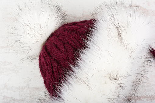 Red knitted winter hat with fur on white wooden background