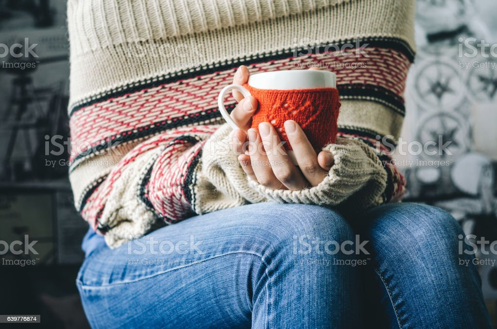 Red Knitted woolen cup with heart pattern in female hands. stock photo
