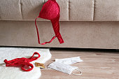 istock Red lace panties, bra, condom and medical masks on the fur rug on a floor near sofa 1214121054