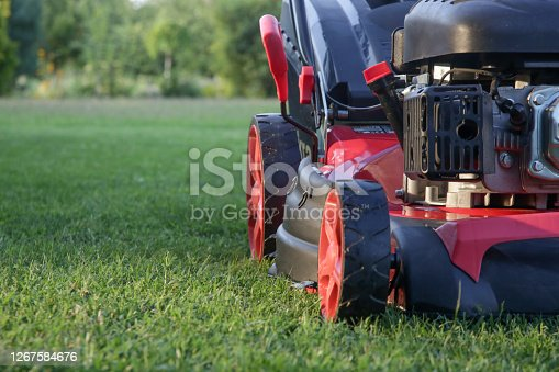 istock Red lawn mower on the meadow, close up 1267584676