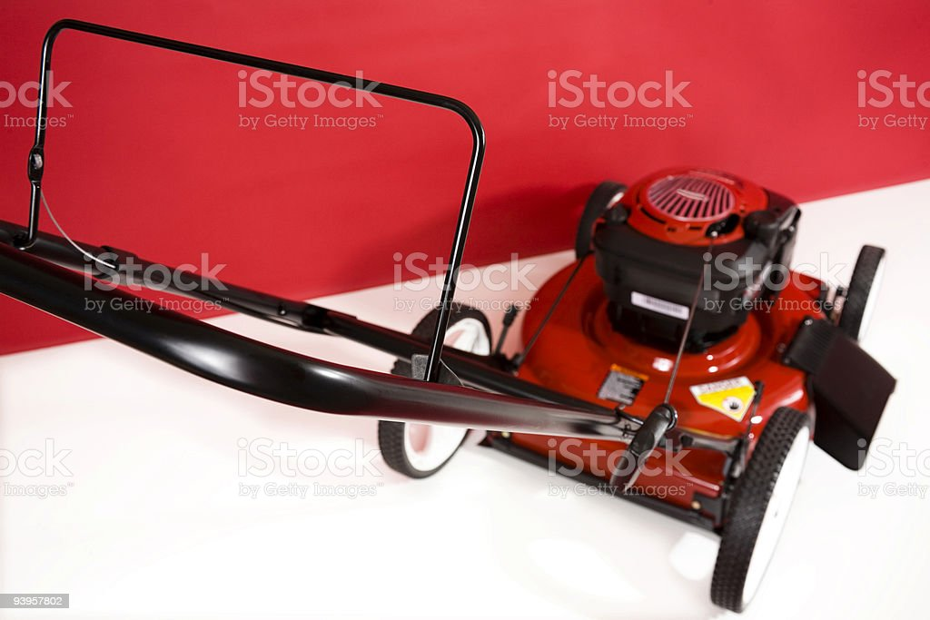 Red Lawnmower against a crimsom and white background. royalty-free stock photo