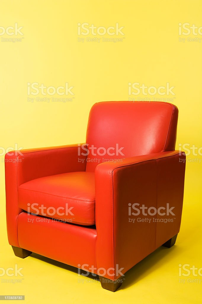 Red leather arm chair on a yellow background stock photo