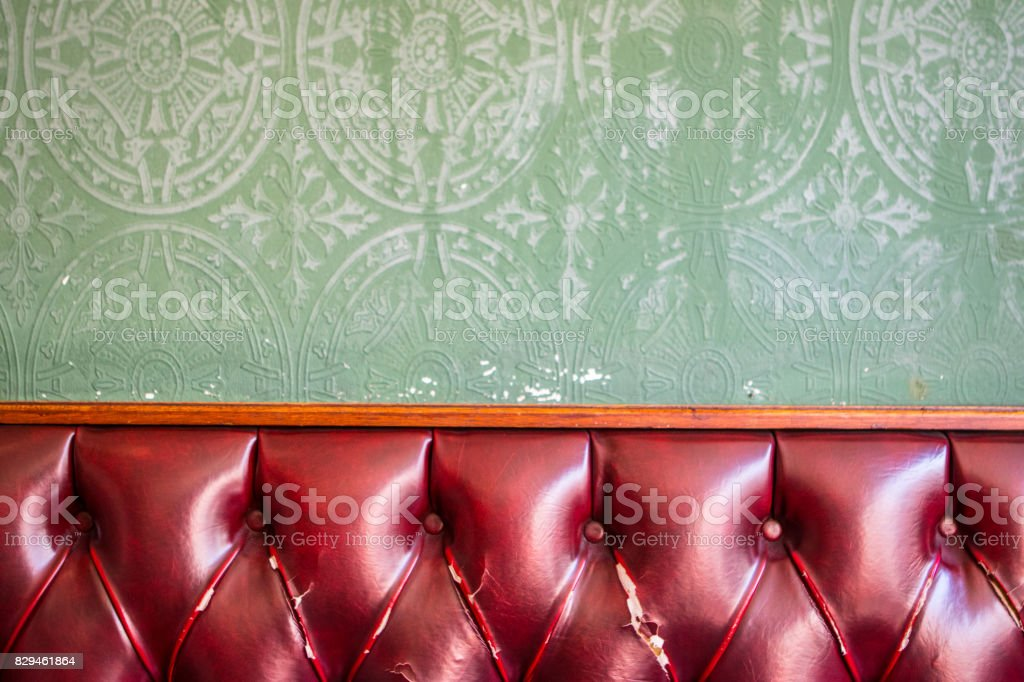 Red leather backrest with green back wall stock photo