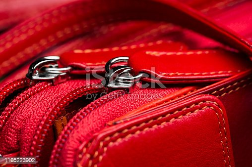 Red leather bag with zipper, shoulder strap and stitches, woman accessories, fashion industry, macro shot, selective focus