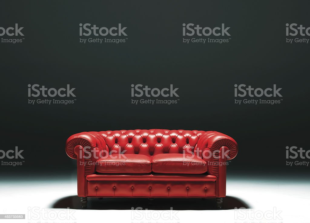 Red Leather Chester sofa in empty room with intense shadows stock photo