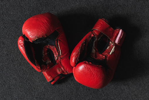 Red leather, old boxing gloves on a dark background.