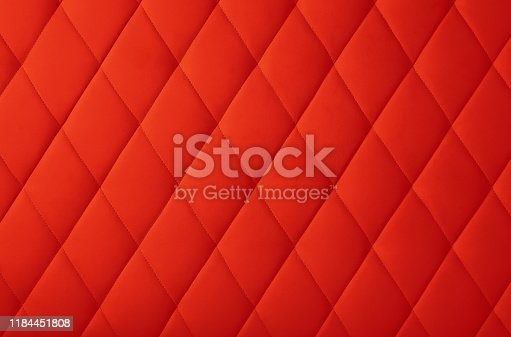 Background texture of scarlet red genuine leather soft tufted furniture or wall panel upholstery with deep diamond pattern, close up