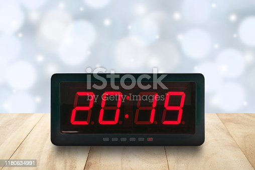 1025550352 istock photo red led light illuminated number 2019 on digital electric alarm clock screen on brown wood table top with defocused pastel blue and white Christmas lights bokeh background 1180634991