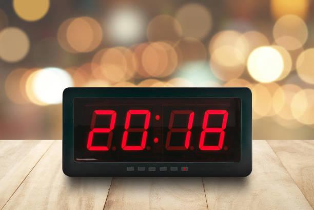 rote led licht beleuchteten zahlen 2018 auf digitalen elektrischen wecker gesicht auf braune hölzerne tischplatte mit defokussierten bunte weihnachten lichter bokeh hintergrund - led uhr stock-fotos und bilder