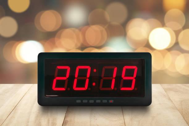 rote led licht beleuchteten zahlen 2019 auf digitalen elektrischen wecker gesicht auf braune hölzerne tischplatte mit defokussierten bunte weihnachten lichter bokeh hintergrund - led uhr stock-fotos und bilder